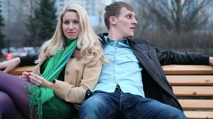 Romantic young couple sit on bench and dream