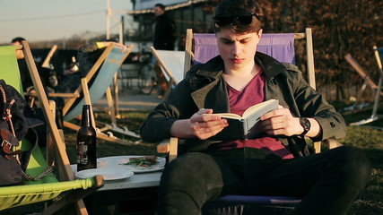 Student reading book and drinking beer in outdoor bar