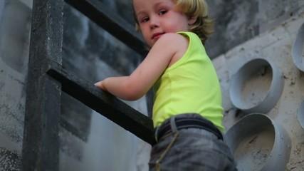 Cute little boy climb on ladder in studio with gray walls