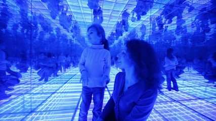Mother and daughter have fun in a mirrored room with blue lights
