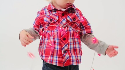 Cute little boy in modern clothes wrapped the garland