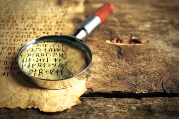 Grunge paper with hieroglyphics with magnifier