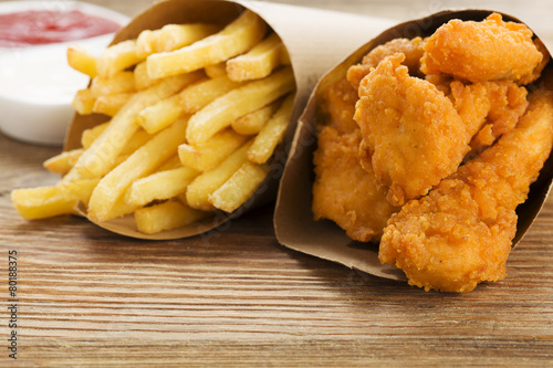 Poster Nuggets and chips served in a paper bag with a dip