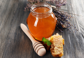 Delicious honey with honeycomb on table close-up