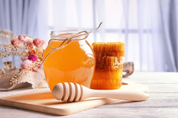 Delicious honey on table on light background