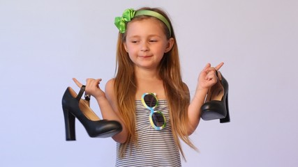 little girl with spectacles on dress in green rim holds in each hand on big black shoe