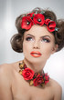 Portrait of beautiful girl in studio with red flowers in hair