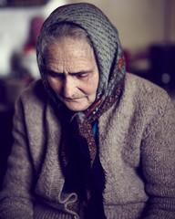 Closeup of an old sad woman indoor