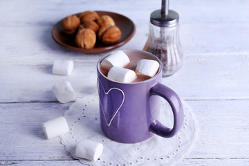 Cup of cocoa with marshmallows and cookies on wooden background