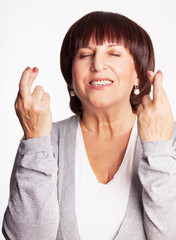 Mature woman with crossed fingers