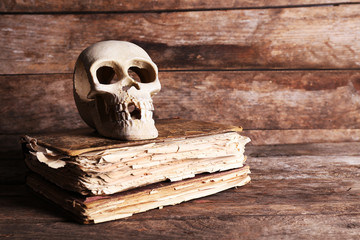 Still life with human skull and retro book on wooden background