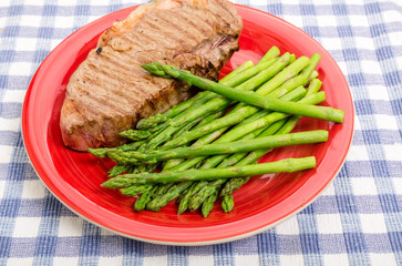 Strip Steak and Asparagus on Red Plate