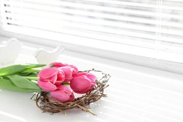 Pink beautiful tulips on windowsill with sunlight