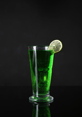 Flaming green cocktail on dark background