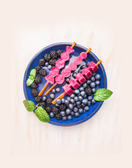 Ice cream pops with  blackberries and blueberries in blue plate