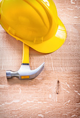 claw hammer and yellow helmet on wooden board construction conce