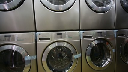 Rows of stainless washing machine in modern laundry