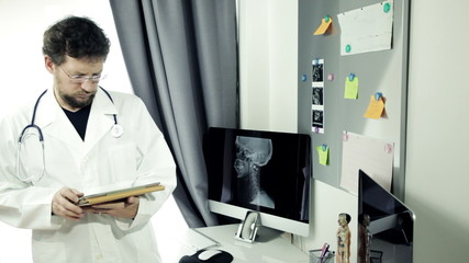 Doctor standing in office working with tablet thinking