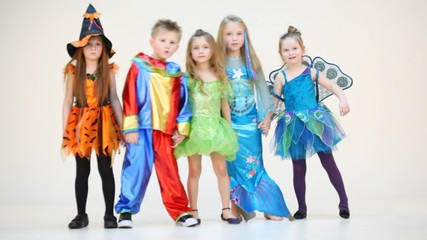 Five children in costumes swinging holding hands isolated