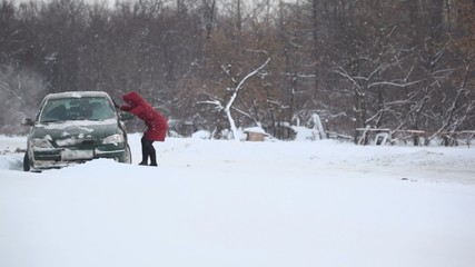 Woman helps to release car from snow trap on country road