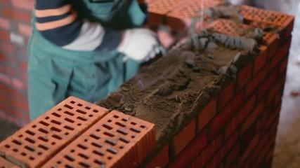 Worker puts bricks during brickwork with trowel, closeup view