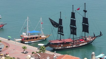 Ship with black pirate sails and boats docked at berth