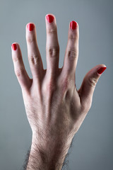 Man's Hand with Red Nail Polish on Gray Background