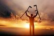 Leinwandbild Motiv A disabled man raising his crutches at sunset. Medical miracle.