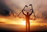 A disabled man raising his crutches at sunset. Medical miracle.
