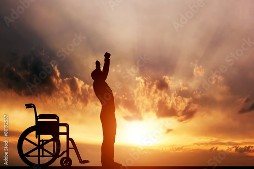 Leinwanddruck Bild A disabled man standing up from wheelchair. Medical miracle.