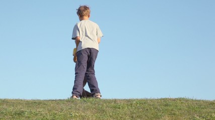 Two kids boy with little girl hold hands and circling, then run closer by grass hill at sunny summer day
