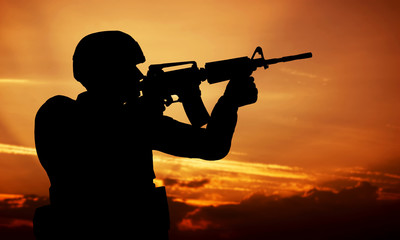 Soldier shooting with his weapon, rifle at sunset. War
