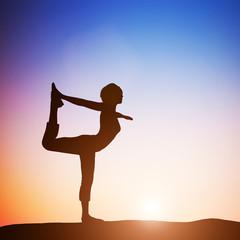 Woman in the dancer yoga pose meditating at sunset. Zen