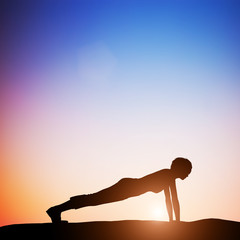 Woman in plank yoga pose meditating at sunset. Zen