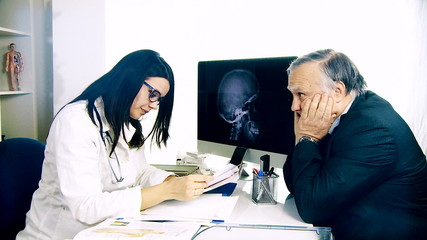 Female doctor giving good news to senior patient in office