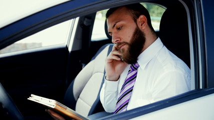 Handsome man with beard working in car with phone and tablet.
