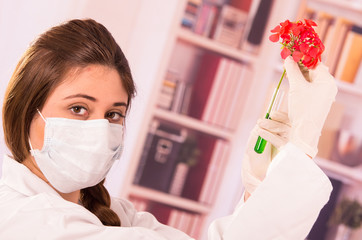 young female biologist experimenting with red flower