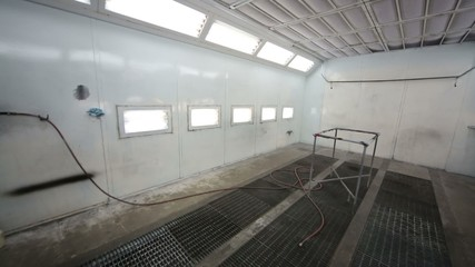 Small empty paint-spraying booth with grey metal walls for cars