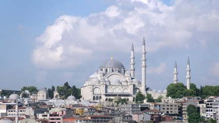 Suleymaniye Mosque stands against city landscape and blue sky, time lapse
