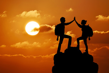 Silhouette of two people man girl success on  mountain