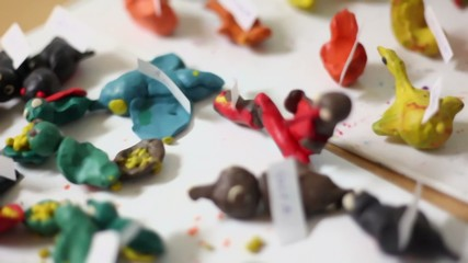 Hand made colorful toys from plasticine lay on table