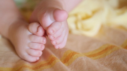 legs with fingers of small baby lie on cover close up
