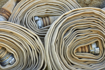 Old rolled fire hoses with nozzles