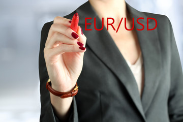 Businesswoman drawing   eur and usd on  a virtual  graph by  a