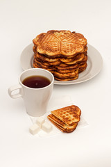 Homemade waffles on the plate and a cup of tea.