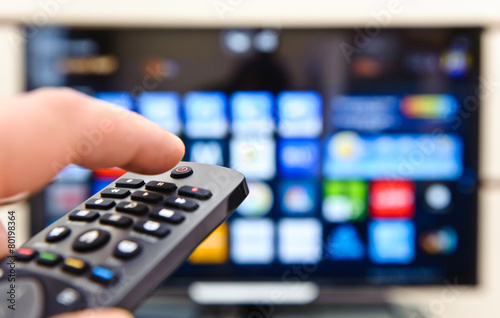Leinwanddruck Bild Smart tv and hand pressing remote control