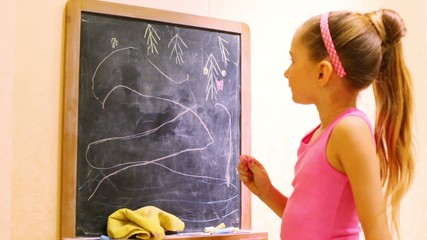 A girl in pink shirt draws spruces on a blackboard with chalks