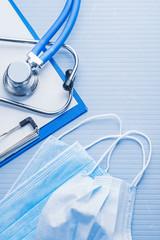 masks clipboard stethoscope on blue background medical concept