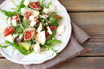Crispy salad with arugula, sliced ​​pears and figs on a whit