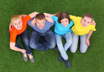 Group of young  people lying on green grass